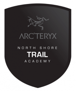 "Logo for the NSMBA Arc'teryx Trail Academy which is a black crest with the Arc'teryx bird logo at the top and the the below states ""Arc'teryx North Shore Trail Academy"