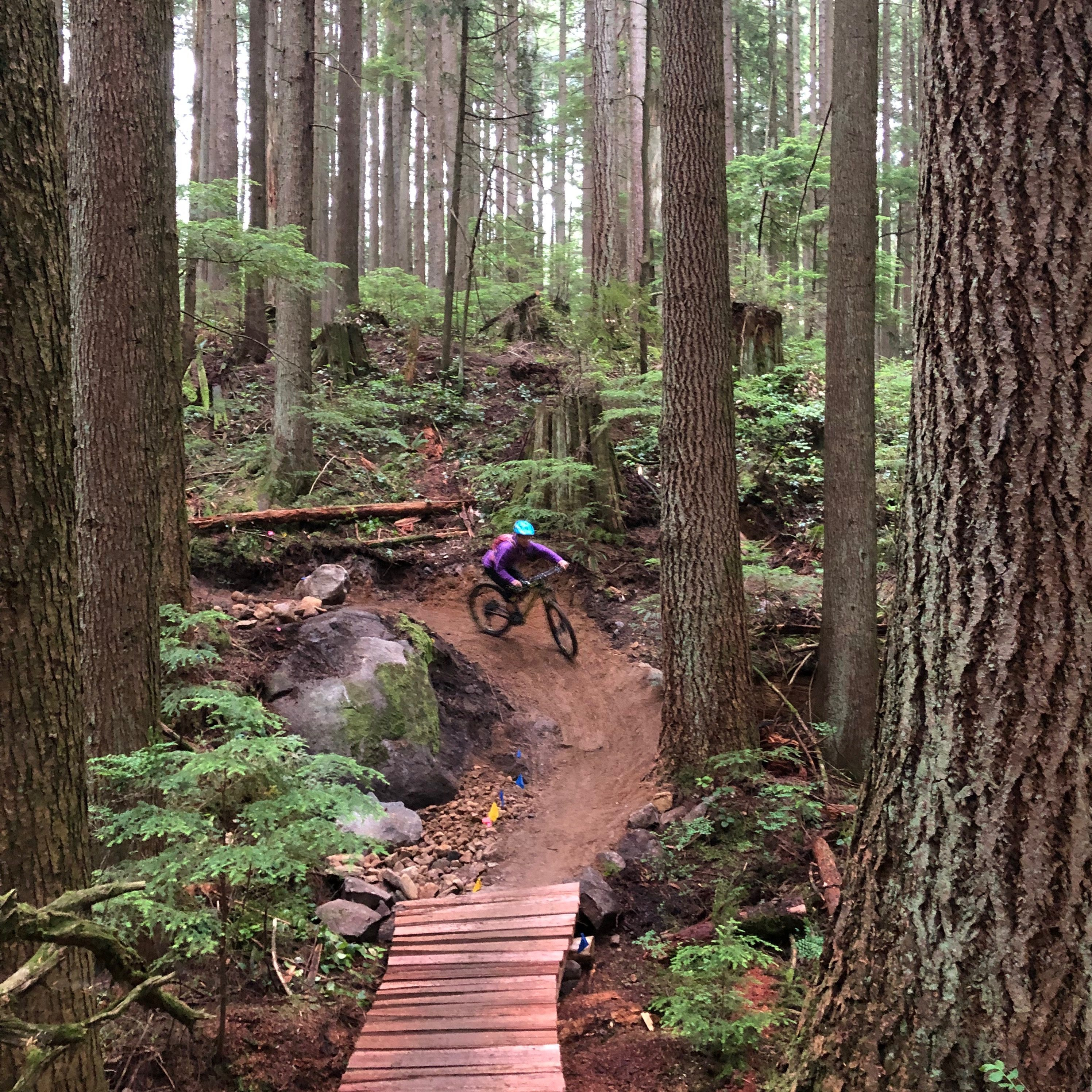 A mountain biking riding through a corner down a fresh section of trail towards the viewer