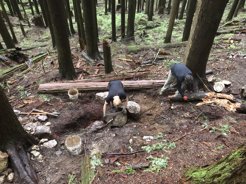 Two volunteers are placing large rock to form the foundation of a retaining wall that will hold up the edge of the trail.