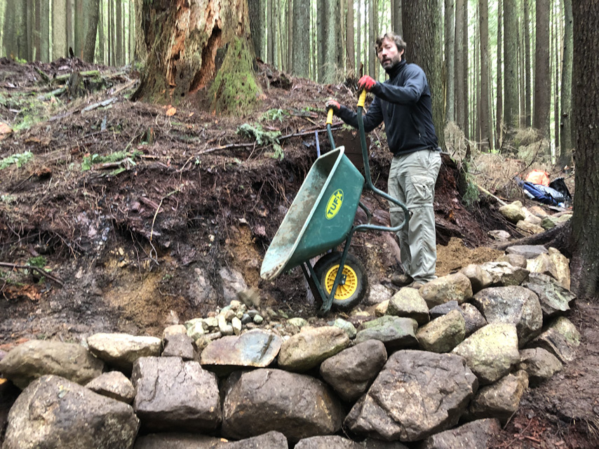 A volunteer empties a wheelbarrow full of small rocks to fill up the trail bed.