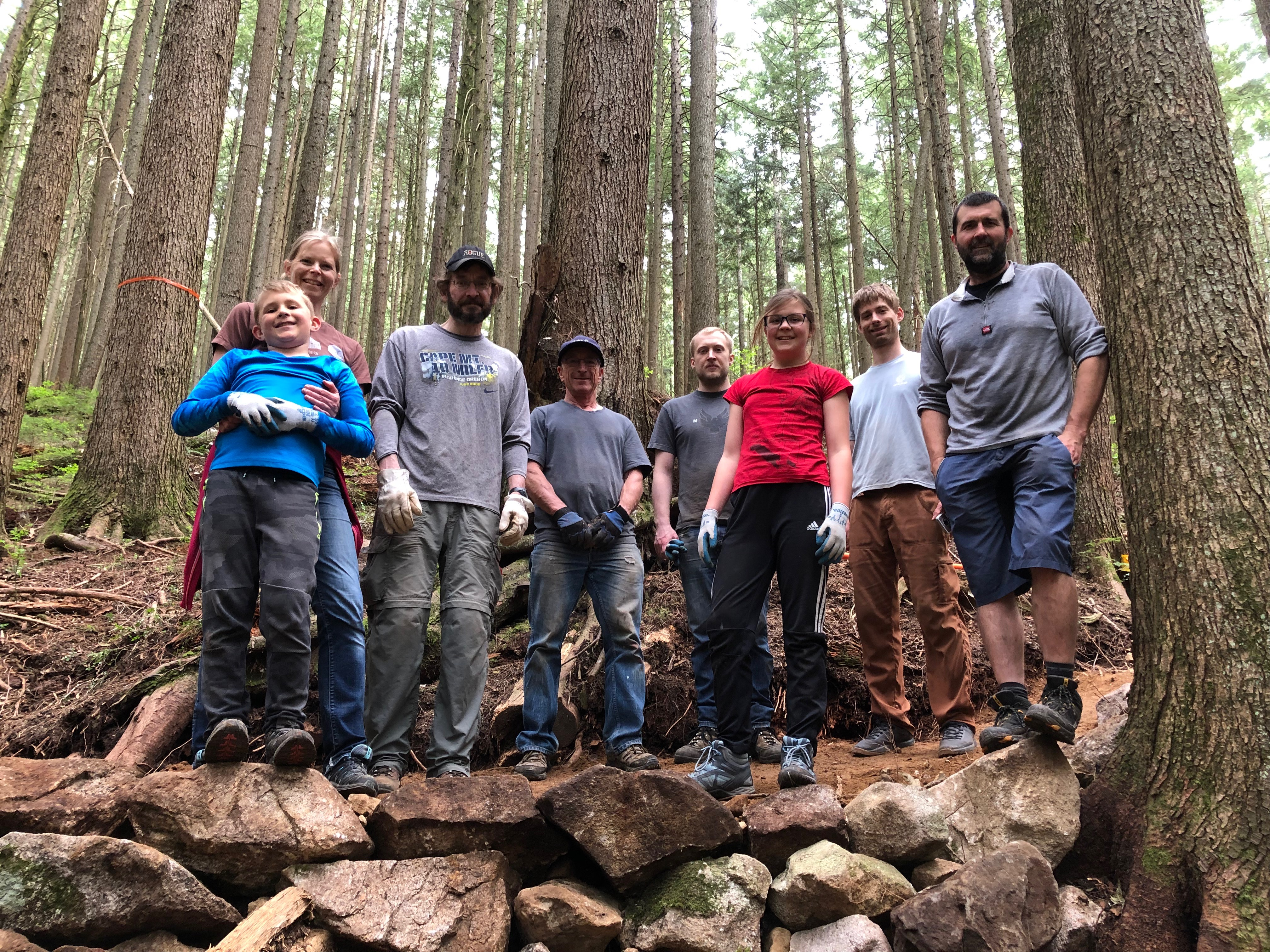 another group of volunteers who helped build the trail, standing on top of a rock retaining wall.