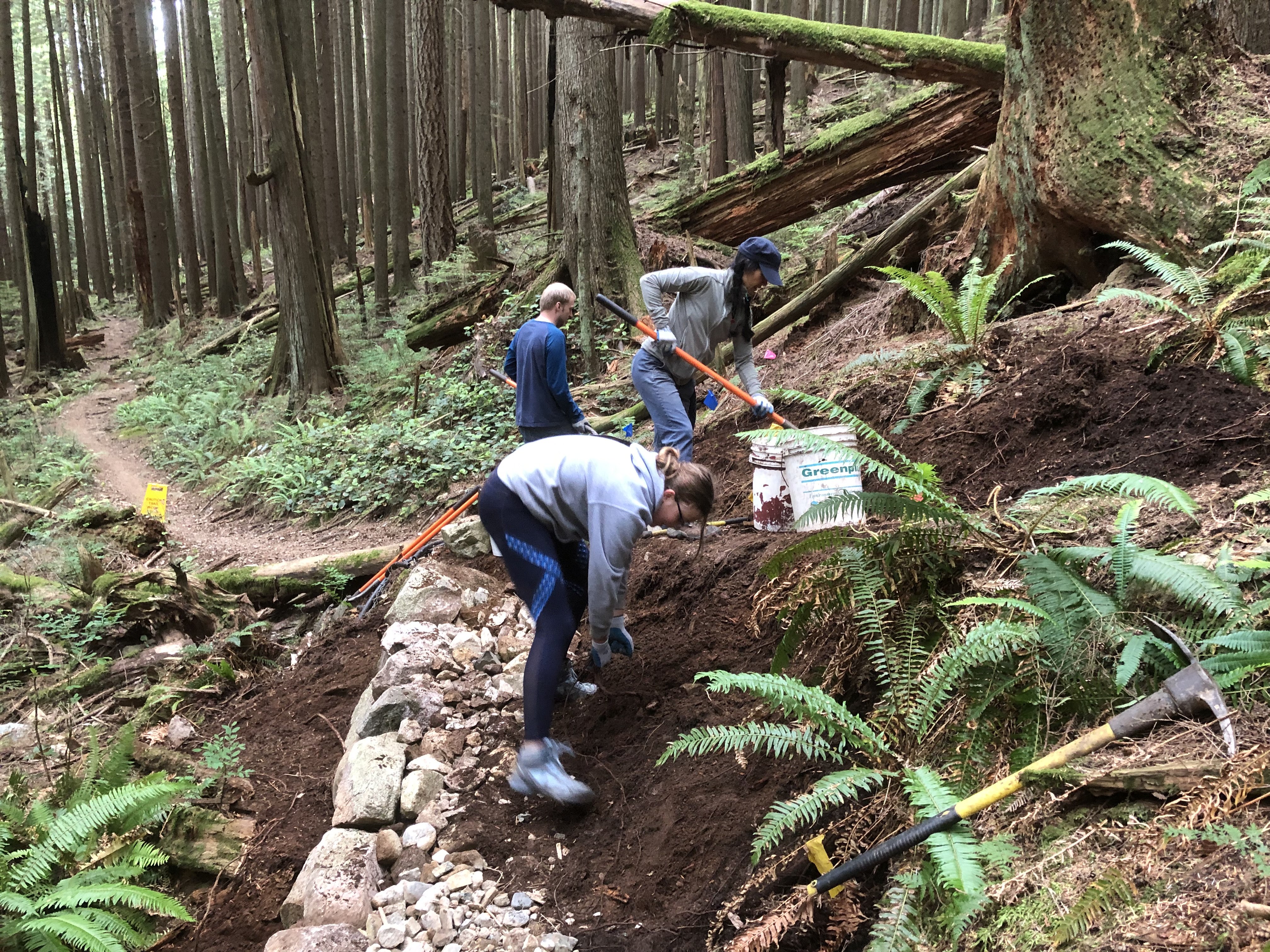 The trail mid way through construction with volunteers moving rock and dirt